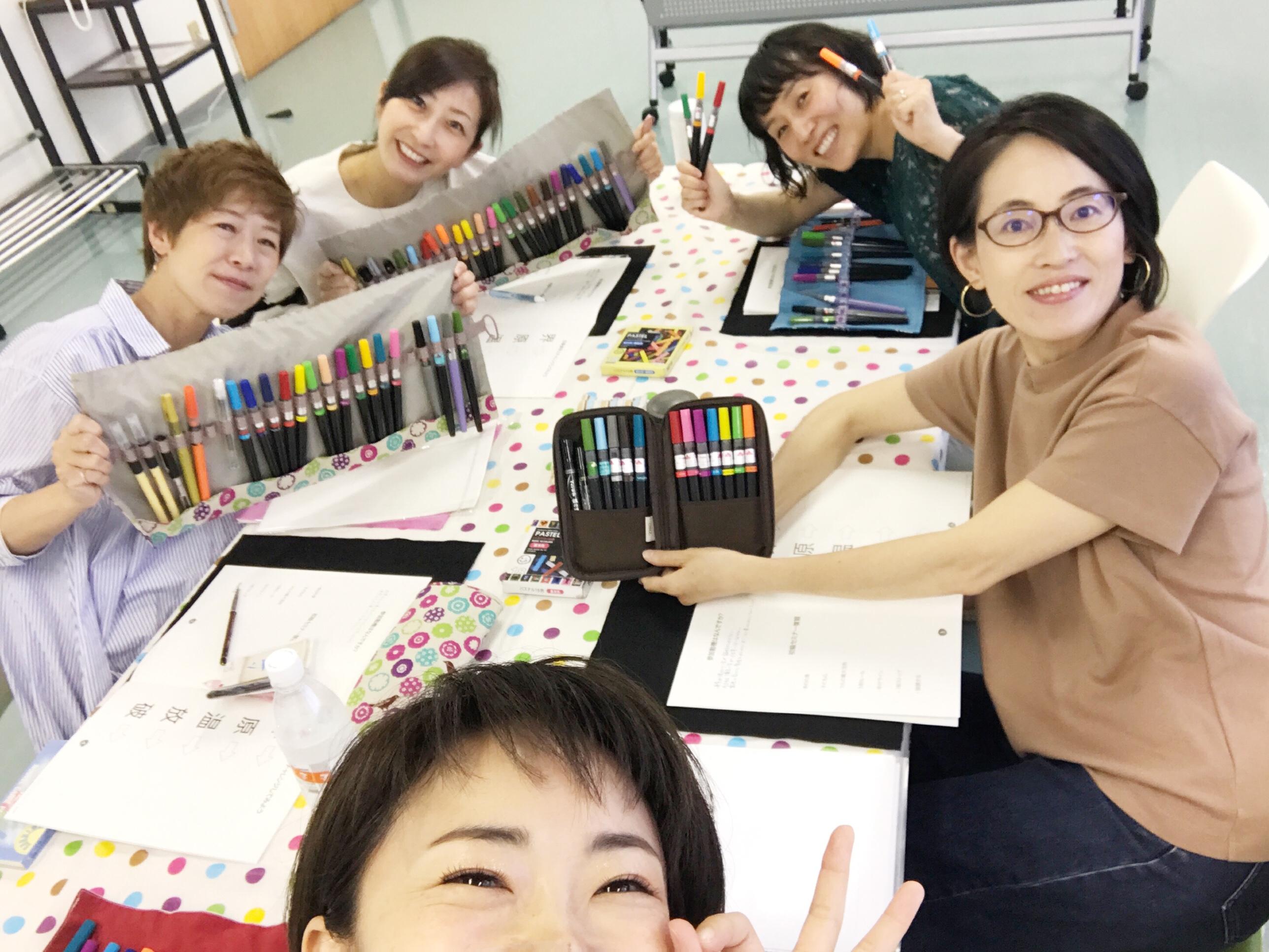 筆ペンをたくさん見せている笑顔の生徒さんたち